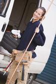 Plumber standing with van smiling — Stock Photo