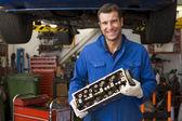 механик, холдинг улыбаясь часть автомобиля — Стоковое фото