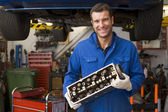 Mechanic holding car part smiling — Stock Photo