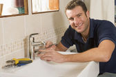 Plumber working on sink smiling — Stockfoto