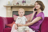 Mother using telephone in living room with baby smiling — Stock Photo