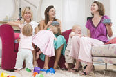 Three mothers in living room with coffee and babies smiling — Stock Photo