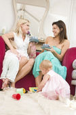Two mothers in living room with babies and coffee smiling — Stock Photo