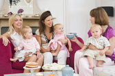 Three mothers in living room with babies and coffee smiling — Stok fotoğraf