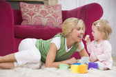 Mother in living room with baby eating banana and smiling — Stock Photo
