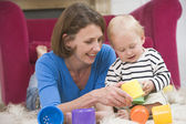 Mother in living room playing with baby smiling — Stock Photo