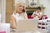 Woman in home office with laptop and telephone with mother and b — Stock Photo