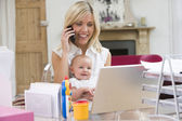 Mother and baby in home office with laptop and telephone — Stock Photo