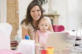 Mère et bébé dans siège social avec ordinateur portable — Photo