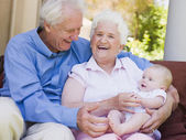 Grandparents outdoors on patio with baby smiling — Stock Photo