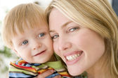 Mother and young boy indoors smiling — Stock Photo