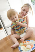 Mother and baby in kitchen eating fruit and vegetables — Stock Photo