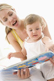 Mother and baby reading book indoors and pointing — Stock Photo