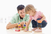 Father and daughter indoors playing and smiling — Stock Photo