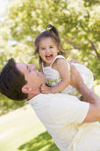 Father holding daughter outdoors smiling — Stock Photo