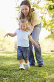 Mother and daughter playing outdoors smiling — Stock Photo