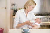 Mother feeding baby in kitchen with coffee — Stock Photo