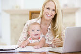Mother and baby in dining room with laptop smiling — 图库照片