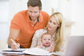 Couple and baby in dining room with laptop — Stock Photo