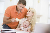 Couple and baby in dining room with laptop and paperwork — Stock Photo