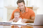 Father and baby in dining room with laptop — Stock Photo