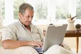 Uomo nel salotto di casa con il portatile — Foto Stock