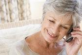 Vrouw binnenshuis met behulp van mobiele telefoon — Stockfoto