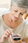Woman using cellular phone indoors smiling — Stock Photo