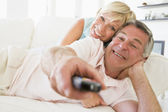 Couple in living room using remote control smiling — Stock Photo