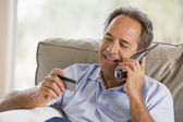 Man indoors using telephone and looking at credit card smiling — Stock Photo
