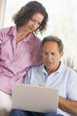 Couple in living room with laptop — Stock Photo