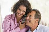 Couple indoors using telephone smiling — Stock Photo