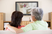 Couple watching television using remote control — Stock Photo