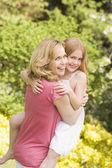 Moeder boekwaarde dochter buitenshuis glimlachen — Stockfoto