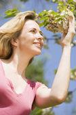 Donna in piedi all'aperto tenendo fiore sorridente — Foto Stock