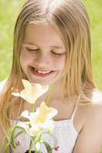 Young girl standing outdoors holding blossom smiling — Stock Photo