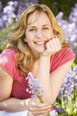 Woman outdoors holding flowers smiling — Stockfoto