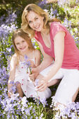 Mother and daughter outdoors holding flowers smiling — Stock Photo
