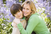 Mother and son outdoors embracing and smiling — Stok fotoğraf