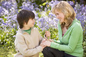 Mother and son outdoors holding flowers smiling — Stock Photo