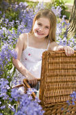Young girl sitting outdoors with picnic basket smiling — Zdjęcie stockowe