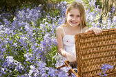 Young girl sitting outdoors with picnic basket smiling — ストック写真