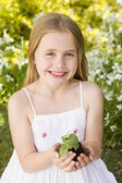 Young girl outdoors holding plant smiling — Stock Photo