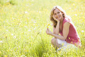 Vrouw buitenshuis met bloem glimlachen — Stockfoto