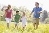 Family walking outdoors holding hands smiling — Stock Photo