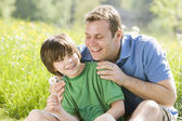 Father and son sitting outdoors with dandelion head smiling — Stock Photo