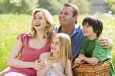 Family sitting outdoors with picnic basket smiling — Stock Photo