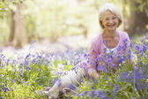 Woman sitting outdoors with flowers smiling — ストック写真