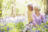 Couple sitting outdoors with flowers smiling — Foto de Stock
