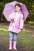 Jong meisje buitenshuis met paraplu glimlachen — Stockfoto